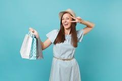 Donna caucasica sorridente alla moda del ritratto bella in vestito da estate, cappello di paglia che tiene le borse dei pacchetti fotografie stock libere da diritti
