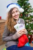 Donna caucasica sorridente attraente con il calzino ed i soldi rossi di Natale dentro Fotografie Stock