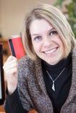 Donna caucasica sorridente che mostra la carta di credito Fotografia Stock Libera da Diritti