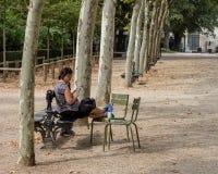Donna caucasica sul banco di parco che tiene un telefono fotografia stock libera da diritti