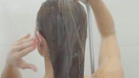 Donna caucasica sveglia che prende una doccia a casa o all'hotel Bello lavaggio della ragazza e godersi di sotto una doccia archivi video