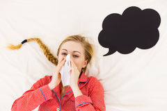 Donna che è malata avendo influenza che si trova sul letto Fotografia Stock
