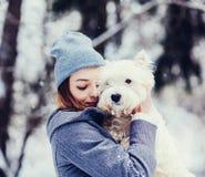 Donna che abbraccia il cane bianco del terrier fotografia stock