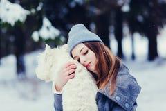 Donna che abbraccia il cane bianco del terrier fotografia stock libera da diritti