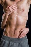 Donna che abbraccia il torso senza camicia del ` s dell'uomo isolato sul nero fotografia stock libera da diritti
