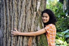 Donna che abbraccia un albero nella foresta Fotografie Stock