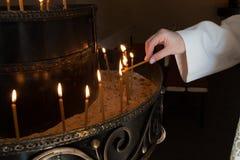 Donna che accende le candele Immagine Stock