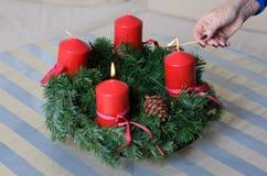 Donna che accende le candele su una corona di Natale Immagine Stock Libera da Diritti