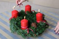 Donna che accende le candele su una corona di Natale Fotografie Stock Libere da Diritti