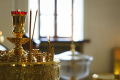 Donna che accende le candele in una chiesa Immagini Stock