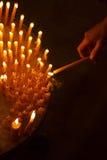 Donna che accende le candele in una chiesa Fotografia Stock