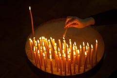 Donna che accende le candele in una chiesa Fotografie Stock