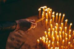 Donna che accende le candele in una chiesa Fotografia Stock Libera da Diritti