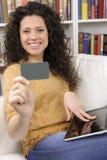 Donna che acquista in linea con l'accreditamento o la scheda del regalo Immagini Stock