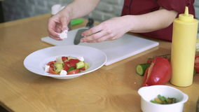 Donna che affetta formaggio per insalata di verdure, preparante su una cucina 4k del ristorante stock footage