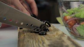 Donna che affetta le olive per pizza su un tavolo da cucina Taglio delle verdure su un tagliere di legno video d archivio