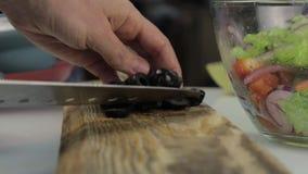 Donna che affetta le olive per pizza su un tavolo da cucina Taglio delle verdure su un tagliere di legno archivi video