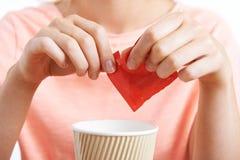 Donna che aggiunge dolcificante artificiale al caffè Fotografia Stock Libera da Diritti