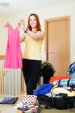 Donna che aggiunge i vestiti nelle valigie Immagini Stock Libere da Diritti