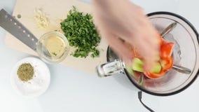 Donna che aggiunge le verdure nel miscelatore cottura della zuppa di verdure fredda sana dell'alimento Vista superiore 4K archivi video