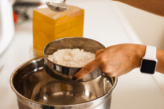 Donna che aggiunge sale alla farina Donna che fa pizza casalinga Vestito in pinny bianco Fotografia Stock
