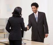 Donna che agita le mani con il collega allo scrittorio Fotografie Stock