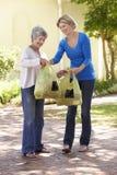 Donna che aiuta femmina senior con acquisto Fotografia Stock