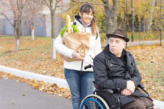 Donna che aiuta un uomo disabile con acquisto Fotografia Stock