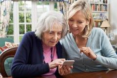 Donna che aiuta vicino senior ad utilizzare telefono cellulare Fotografia Stock