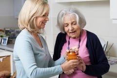 Donna che aiuta vicino senior a rimuovere il coperchio del barattolo Fotografia Stock Libera da Diritti