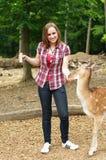 Donna che alimenta un cervo nello zoo Fotografia Stock Libera da Diritti