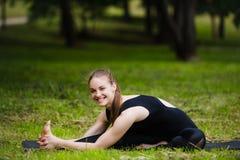 Donna che allunga all'aperto in un parco prima della pratica di yoga Immagini Stock Libere da Diritti