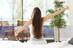 Donna che allunga armi e che sveglia nella camera da letto Immagini Stock Libere da Diritti