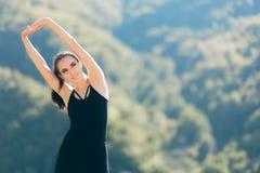 Donna che allunga armi prima della sessione all'aperto di forma fisica di esercizio in natura Immagini Stock