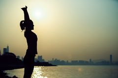 Donna che allunga armi sulla spiaggia di alba Immagini Stock