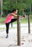 Donna che allunga dentro della coscia su una barra, esercitandosi nel parco Fotografia Stock Libera da Diritti