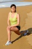 Donna che allunga e che si esercita sulla spiaggia Fotografie Stock Libere da Diritti
