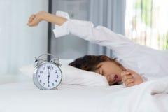 Donna che allunga e che sbadiglia mentre svegliando di mattina con Fotografia Stock