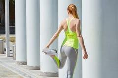 Donna che allunga gamba di piegamento all'aperto, giorno soleggiato Fotografia Stock Libera da Diritti