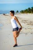 Donna che allunga gamba dopo avere corso alla spiaggia Immagini Stock Libere da Diritti