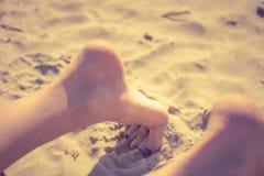 Donna che allunga gamba su una spiaggia rilassata fotografie stock libere da diritti