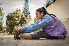 Donna che allunga gamba sul marciapiede urbano Esercitazione della giovane donna Immagine Stock