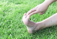Donna che allunga il dito dei piedi di esercizi sul fondo dell'erba verde Immagine Stock