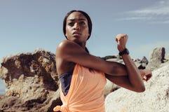 Donna che allunga il suo muscolo del braccio alla spiaggia Fotografia Stock Libera da Diritti