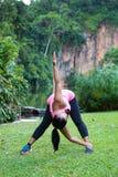 donna che allunga il suo muscolo più lombo-sacrale piegando in avanti e torcendo ad un lato Fotografia Stock