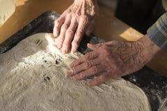 Donna che allunga la pasta cruda della crosta della pizza in pentola Immagini Stock