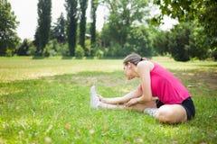 Donna che allunga la sua gamba Immagine Stock Libera da Diritti