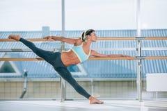 Donna che allunga la sua gamba alla sbarra Fotografia Stock