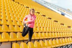 Donna che allunga le gambe allo stadio Immagine Stock
