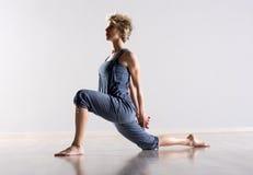 Donna che allunga le gambe ed i muscoli della spalla Immagini Stock